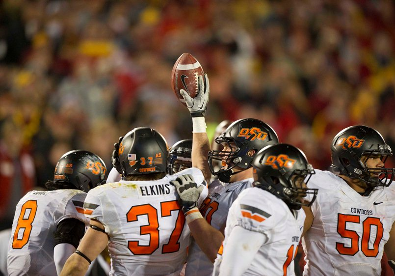 Nov 18, 2011; Ames, IA, USA; Oklahoma State Cowboys linebacker Alex Elkins (37) holds up the football while surrounded by teammates during the second half of a game against the Iowa State Cyclones at Jack Trice Stadium. Iowa State Cyclones defeated the Oklahoma State Cowboys 37-31. Mandatory Credit: Beth Hall-US PRESSWIRE